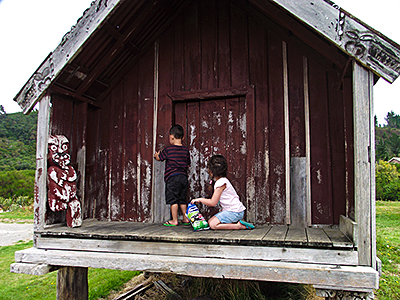 children playing in whare on marae