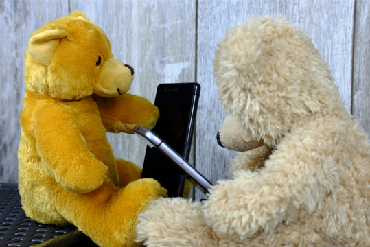 teddies with digital device and pen