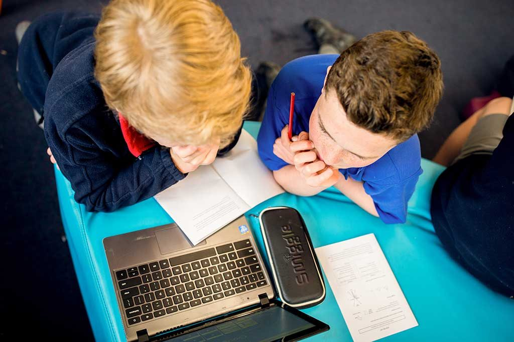 Two boys sit at a table looking at a computer screen