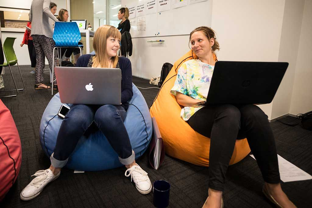 Two women sitting on beanbags with laptops open are looking at each other and smiling