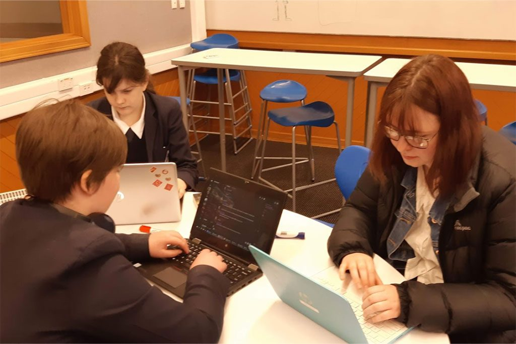 Three high school students use laptops for online gaming
