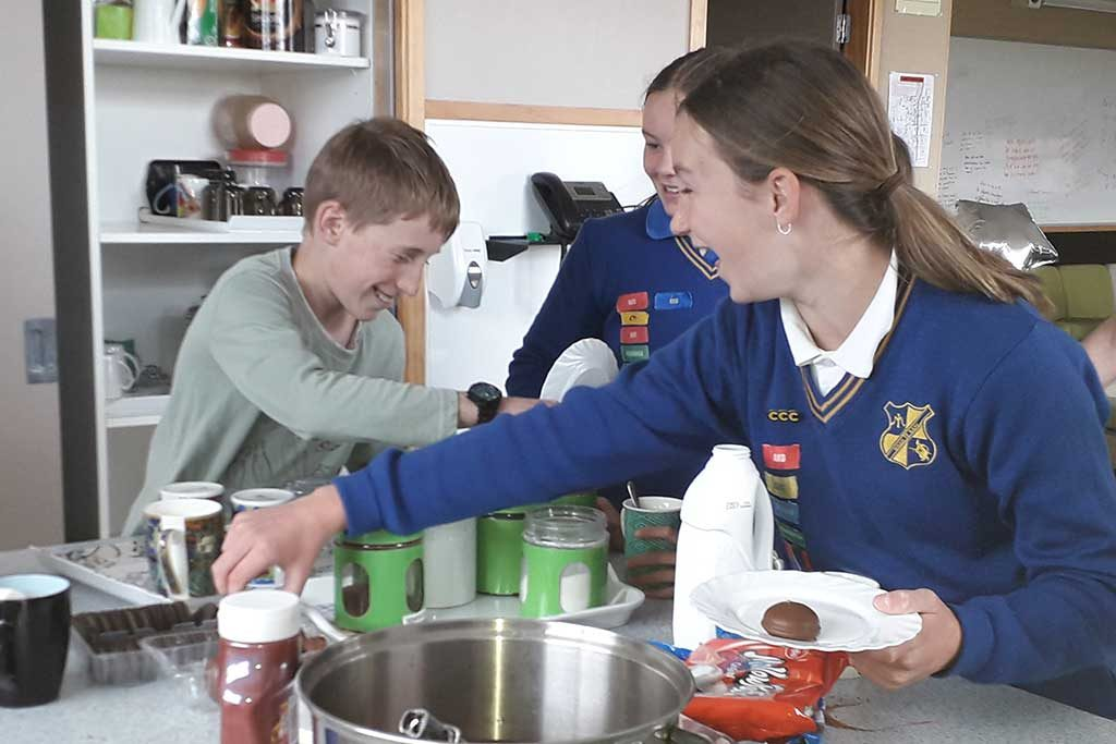 Three students laugh whilst making hot chocolate drinks